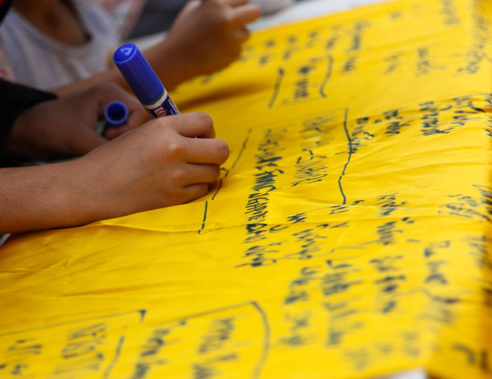 kid writing on fabric with fabric marker