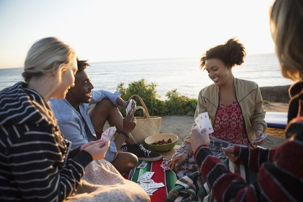 Four young friends playing cards on a beach.