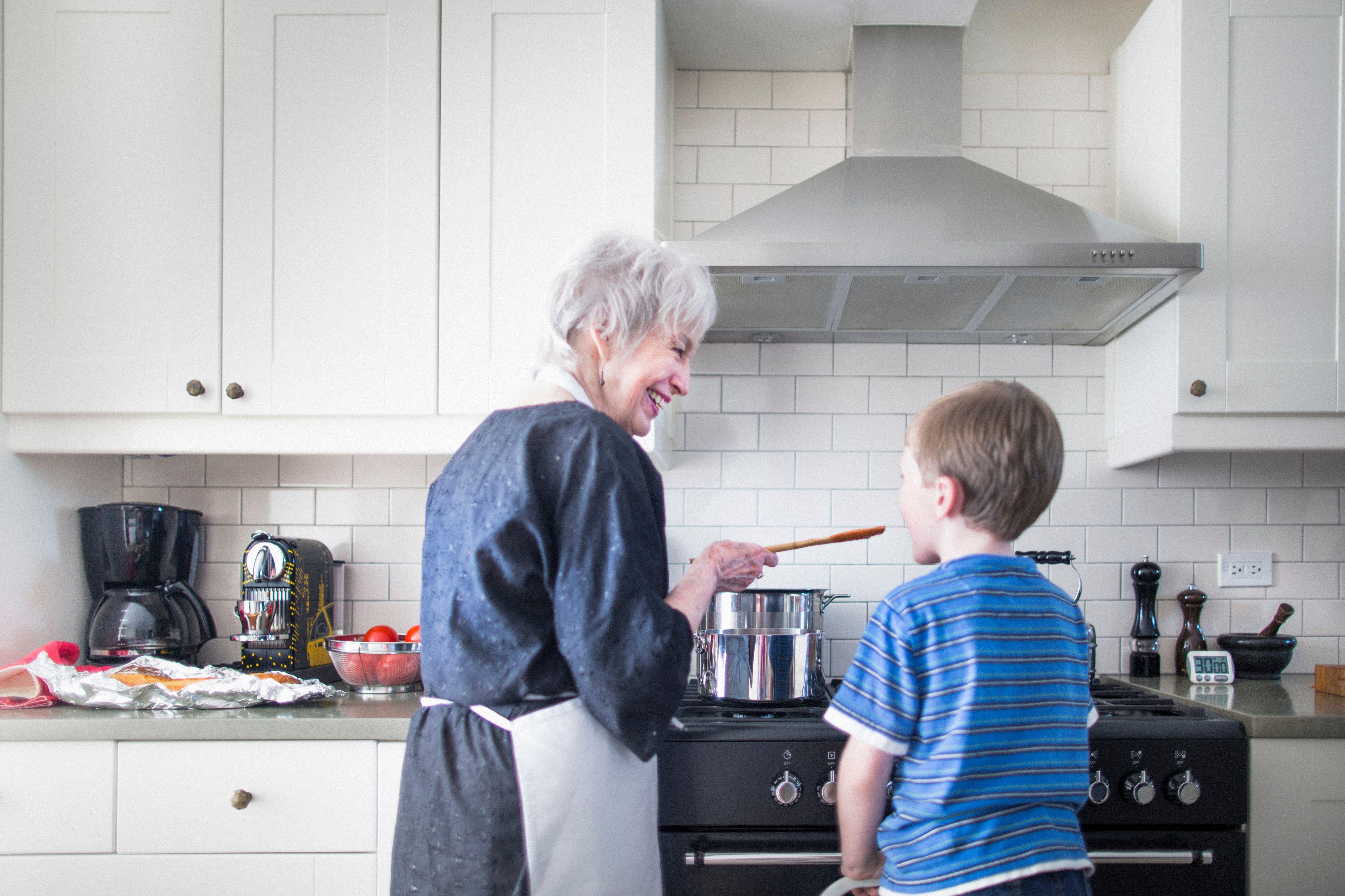 Grandmother and grandson preparing food at home