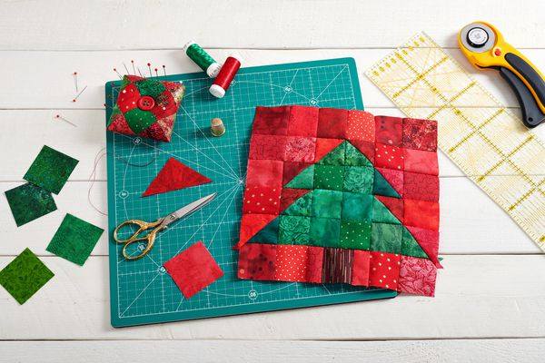 Christmas tree patchwork block, pieces of fabric, quilting and sewing accessories on white wooden background