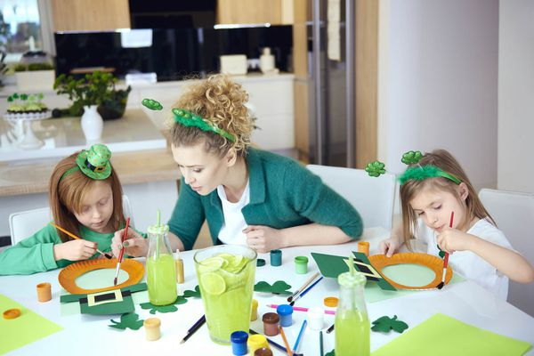 A mom and her children creating St. Patrick's Day crafts