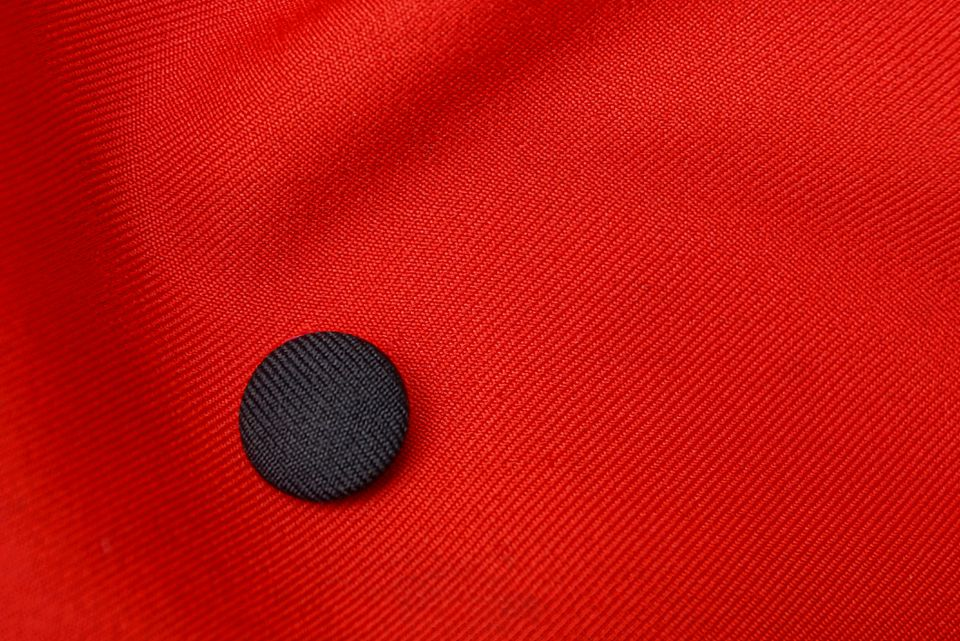 texture of a red fabric with a black round button