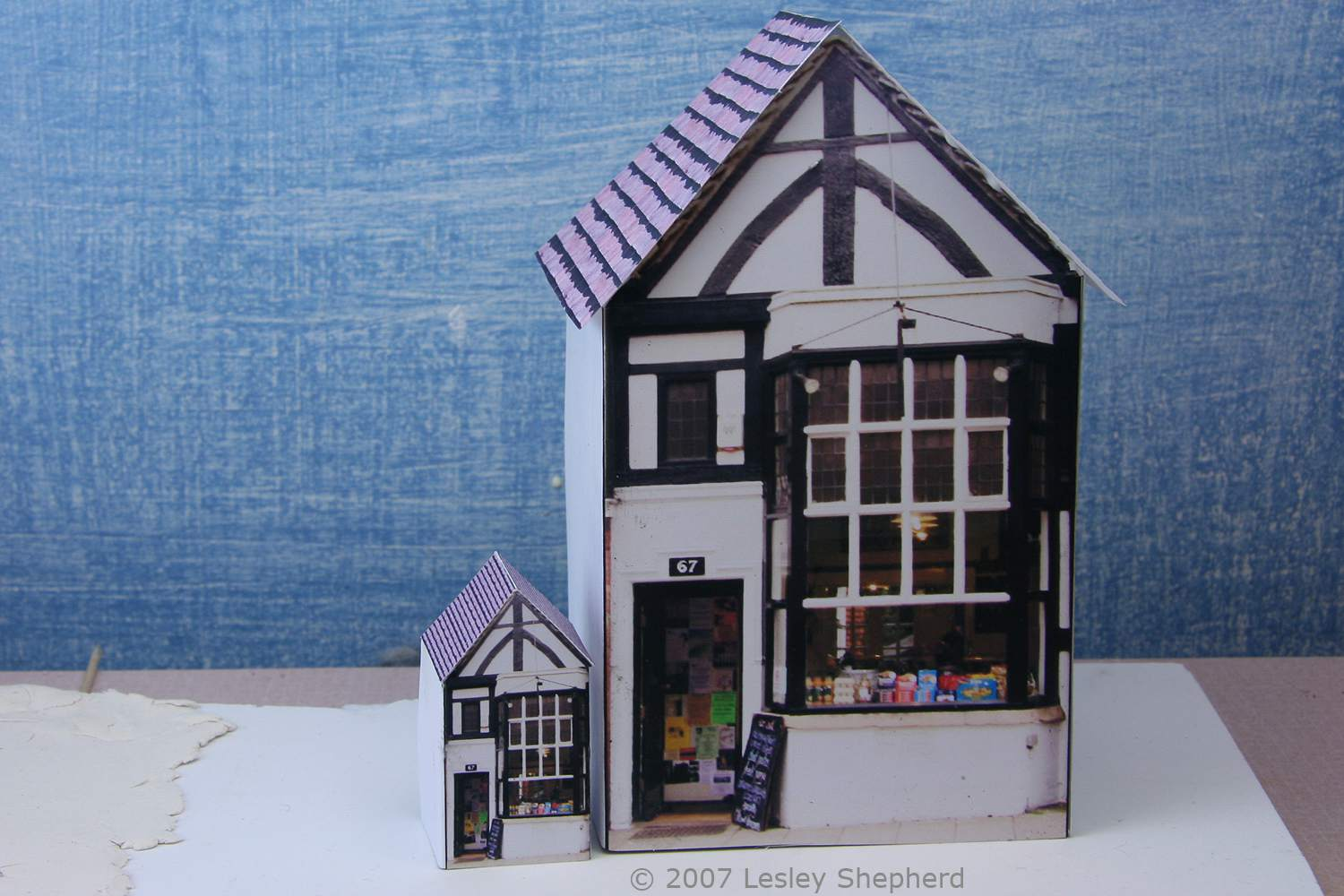 A 1:144 scale printable miniature shop next to one in 1:48 scale.