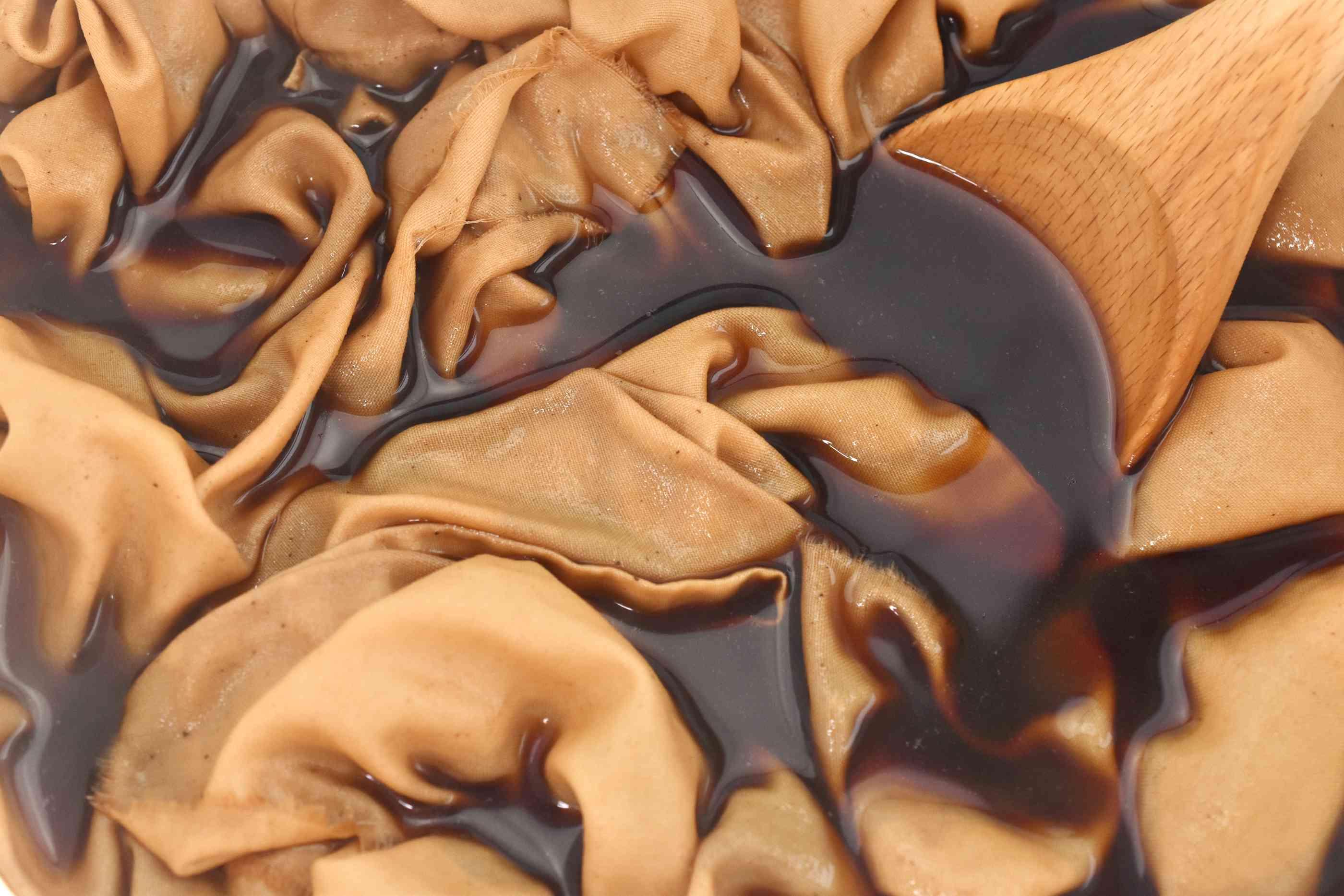 Fabric Being Stirred in a Coffee Dye Bath