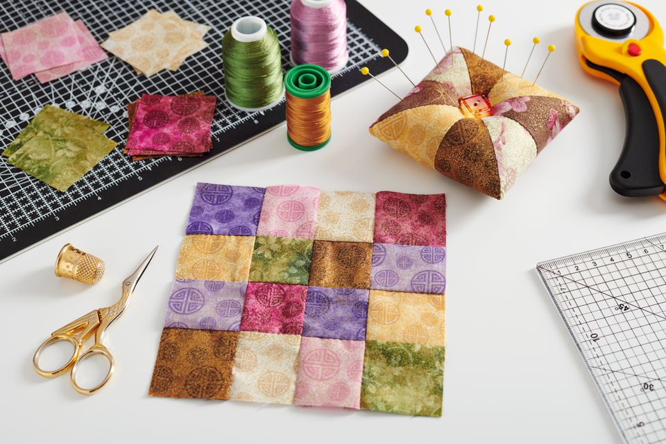 Quilting block from bright square pieces of fabrics, pincushion, stacks of square pieces of fabrics, quilting and sewing accessories