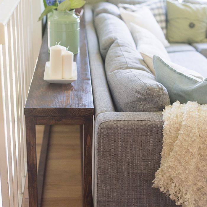 A small console table behind a sofa