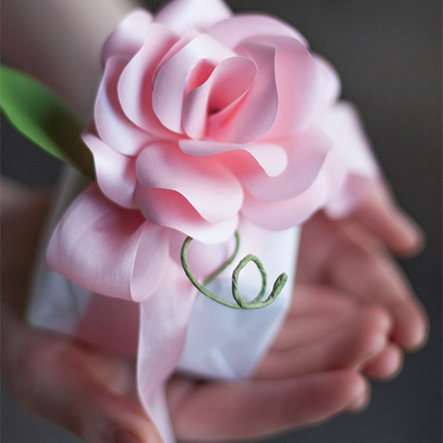 A woman holding a gift topped with a pink paper rose