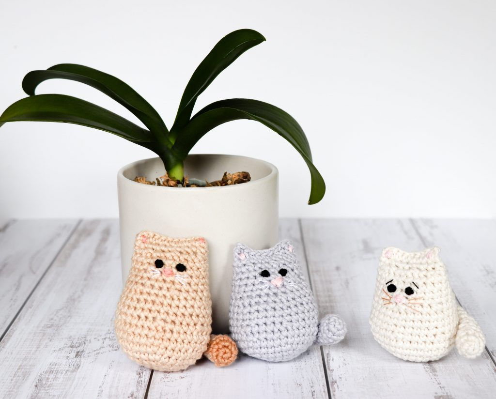 Three small crochet cats with no limbs propped up in front of a plant.
