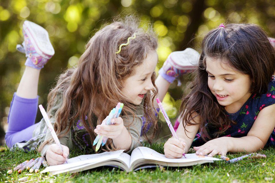 Girls Drawing on Coloring Book While Lying on Field
