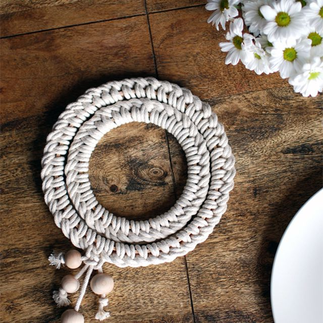 A macrame trivet on a table with flowers