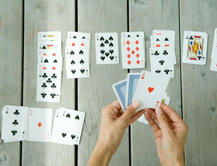 Woman playing solitaire, cropped view of hands and cards