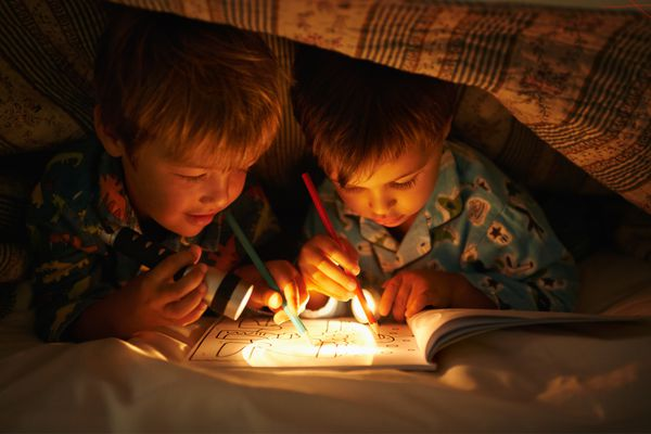 Two boys coloring under the covers at night