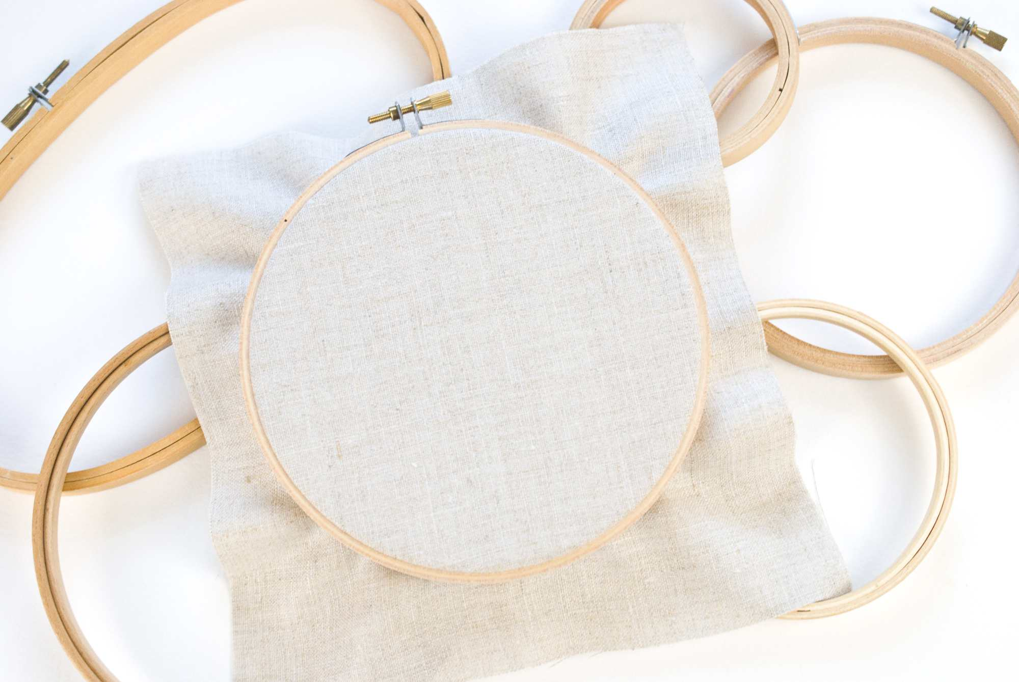 Several embroidery hoops lying on the floor with one holding white fabric.