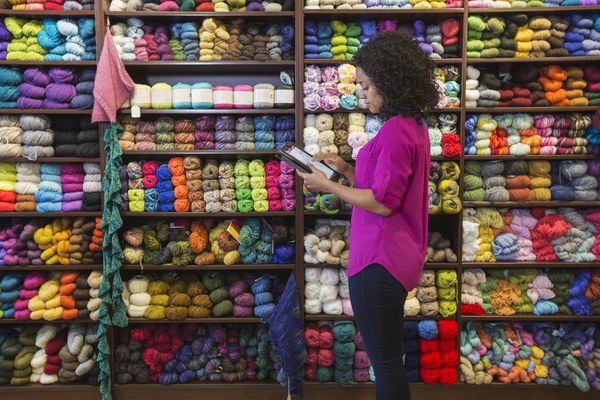 Woman taking inventory in yarn store