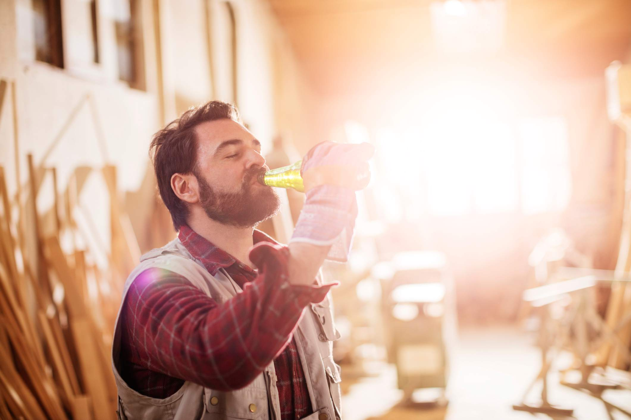 Man drinking a beer in his wood shop