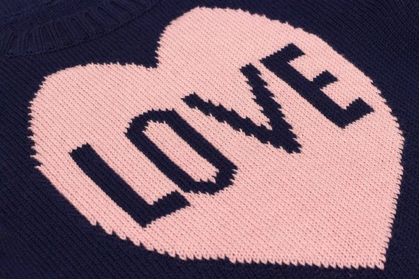 Handmade blue knitted fabric with pink heart and word Love bound on knitting needles as backgroun or texture