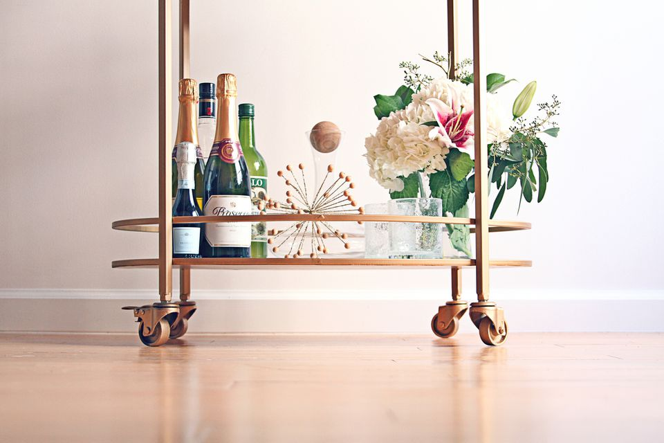 Flowers, decor, and bottles on bar cart