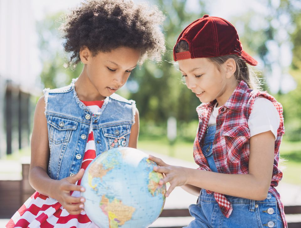 two happy kids looking at a globe
