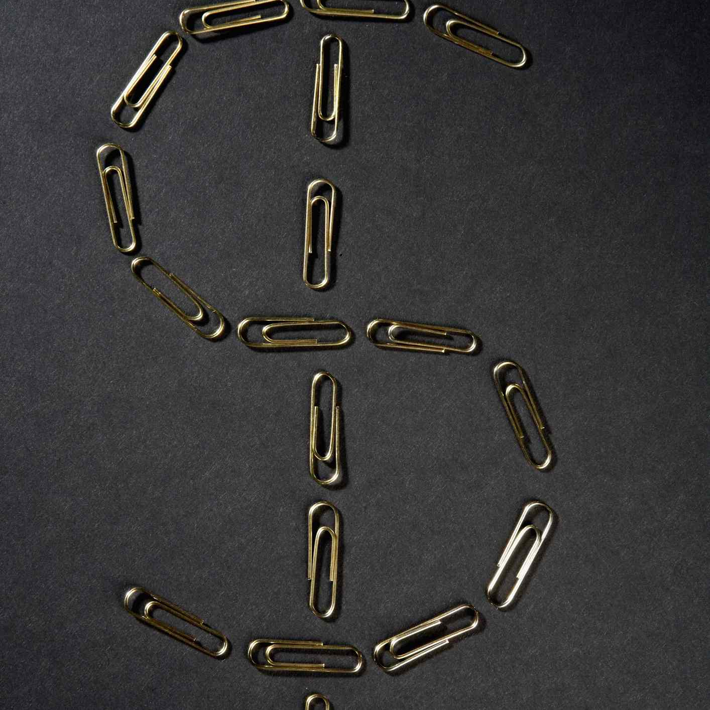 Close-up of paper clips in the shape of Dollar symbol