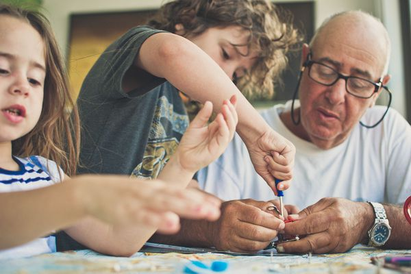 Grandfather Building a Robot With His Grandchildren