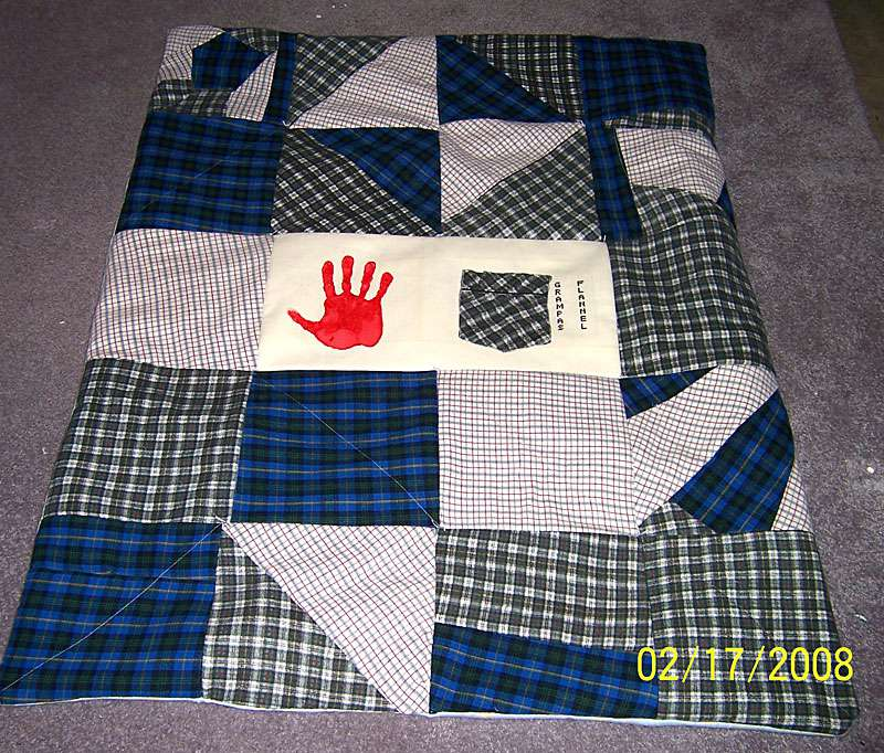 Blue, gray, and white flannel quilt with red handprint sewn into the middle.