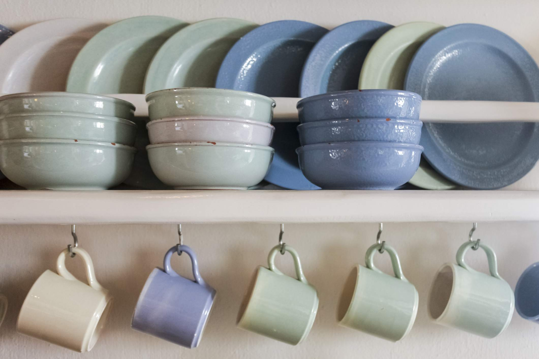 Blue and green clay plates, bowls, and coffee cups on shelf