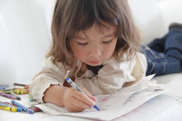 close up of little girl lying on couch coloring