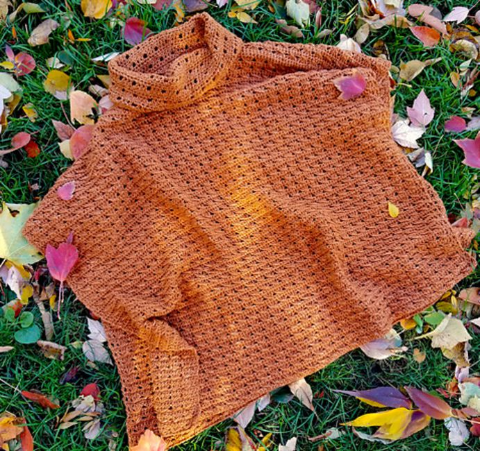 Orange poncho laying on a lawn with colorful leaves