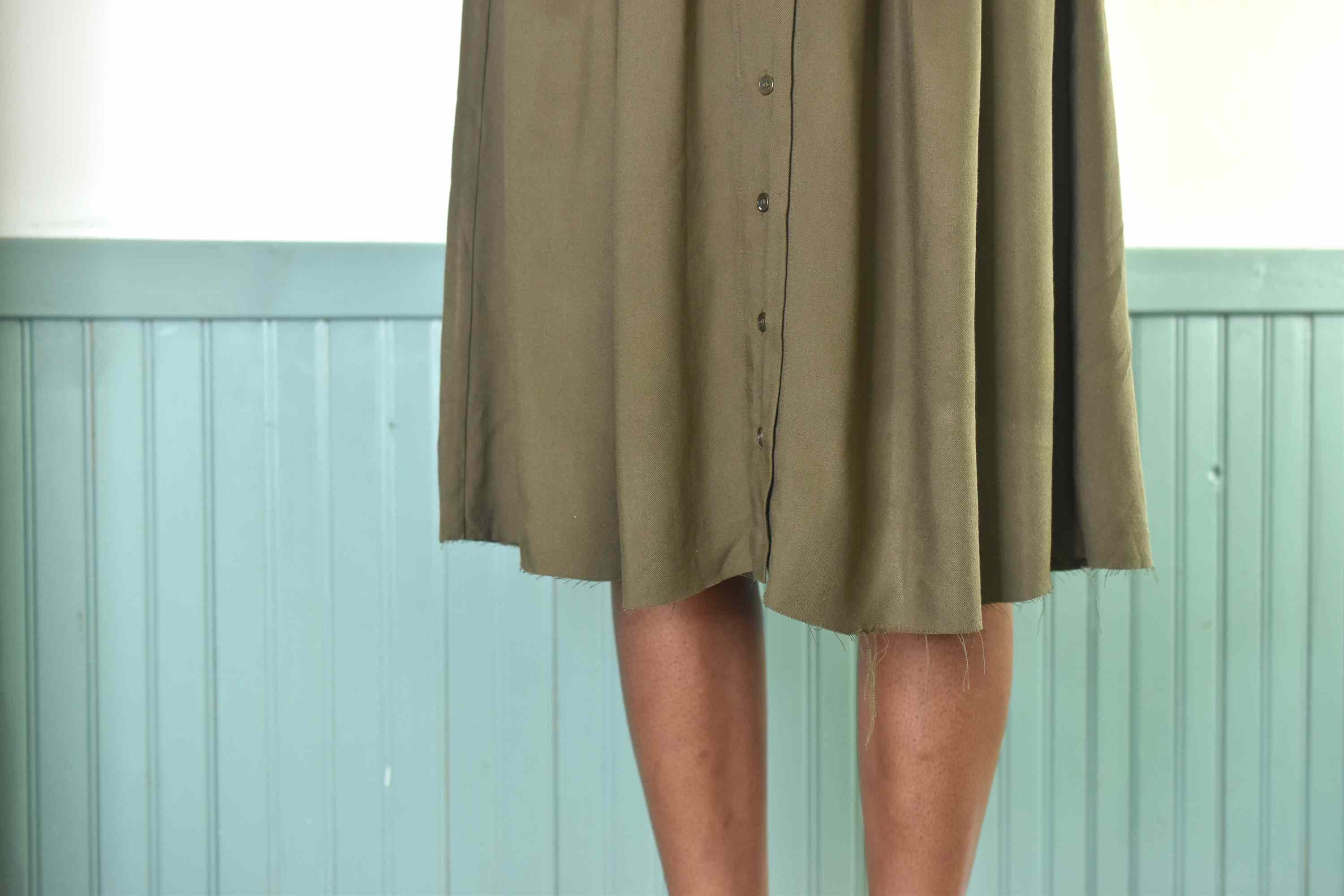 Person wearing a skirt with an unfinished and uneven hem