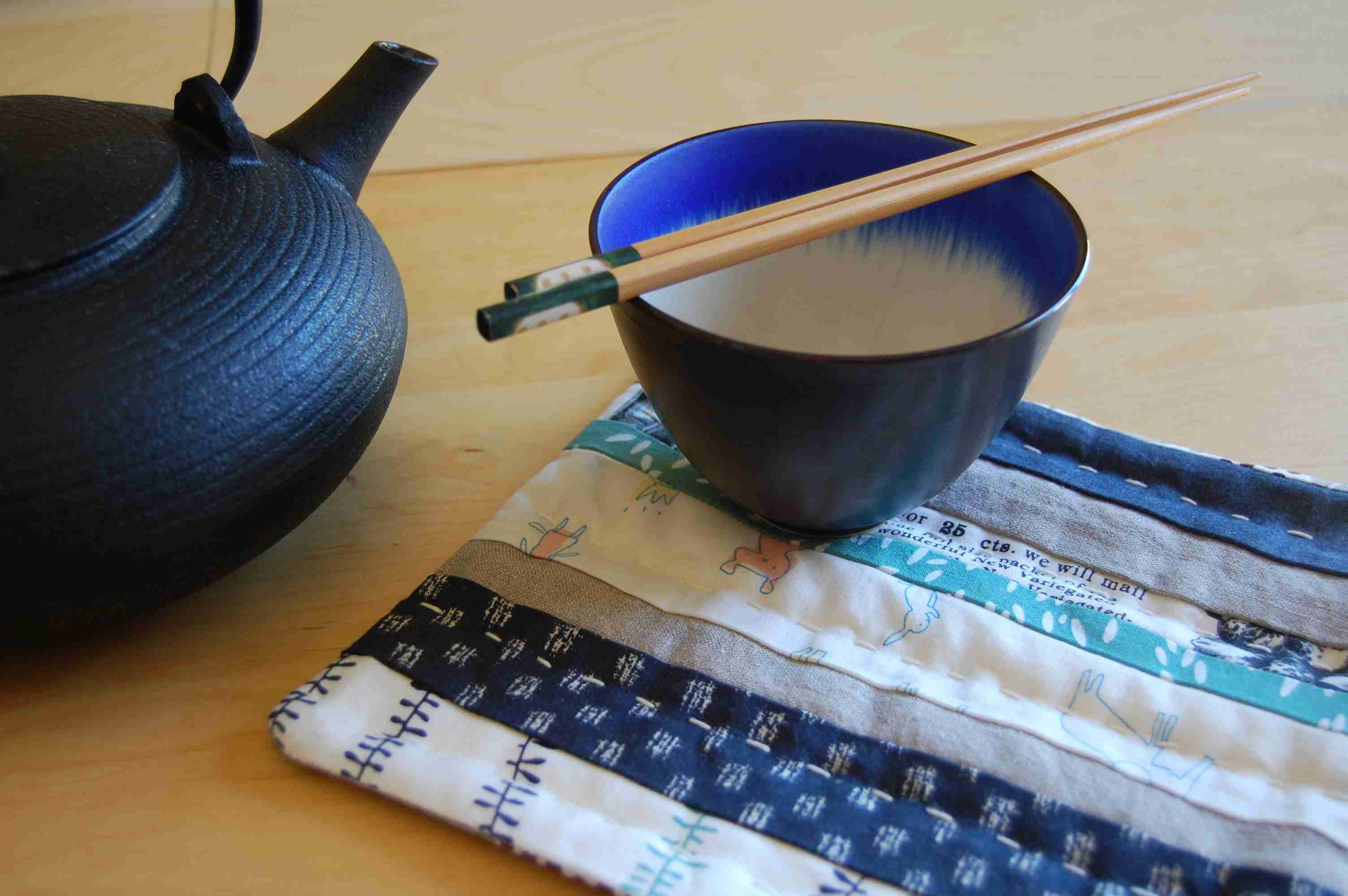 A scrappy pot holder with a bowl, chopsticks, and tea kettle on a table