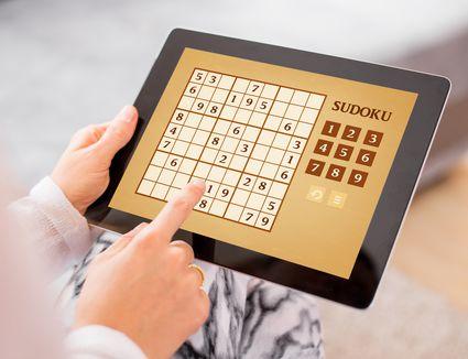 Woman playing Sudoku on tablet computer
