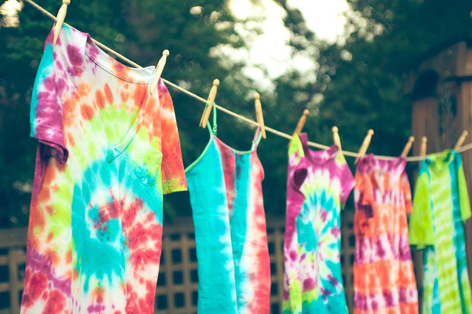 Tie dyed tee shirts hanging from a clothes line.