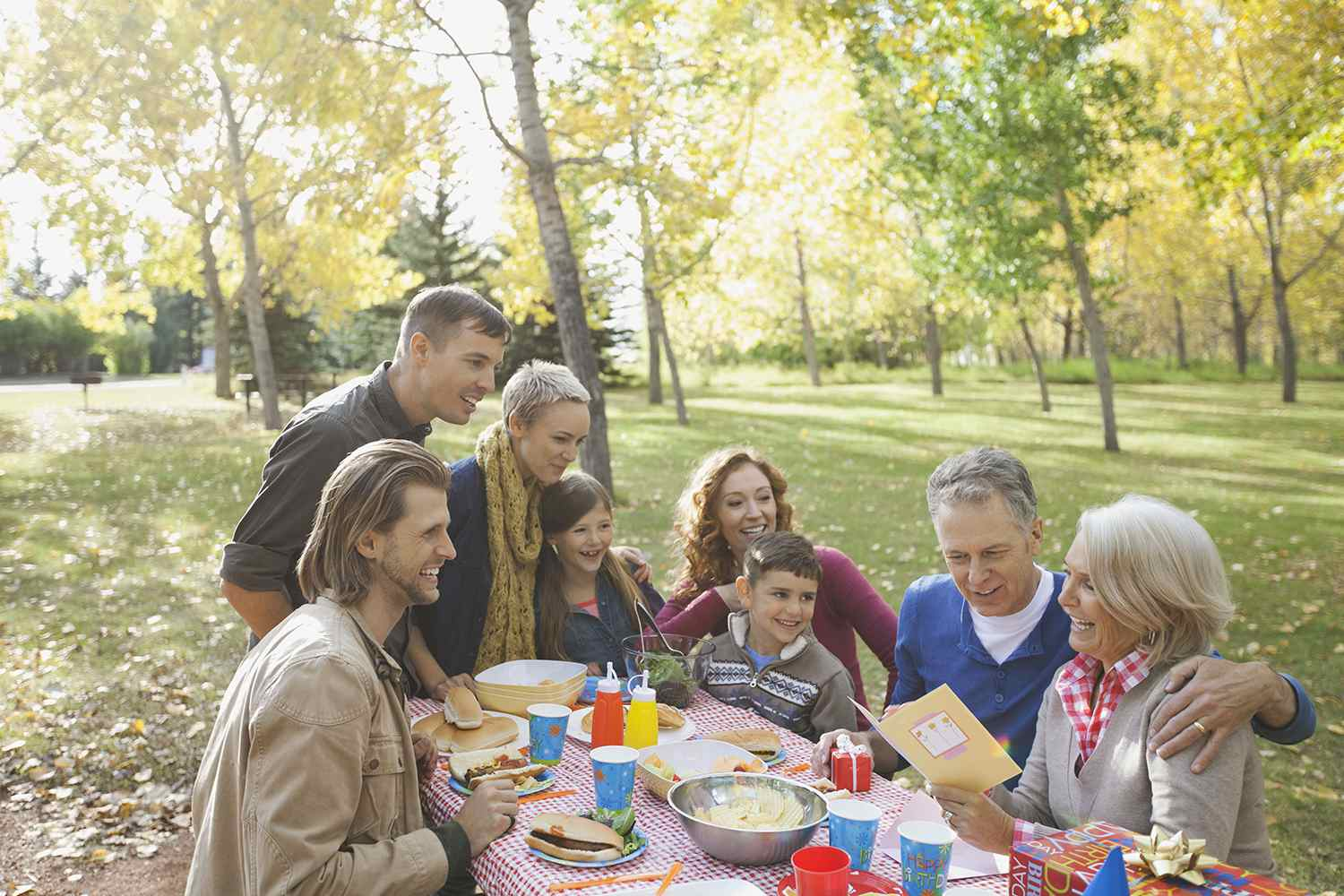 Happy Multi-Generation Listening to Mature Woman Reading Greeting Card in Park