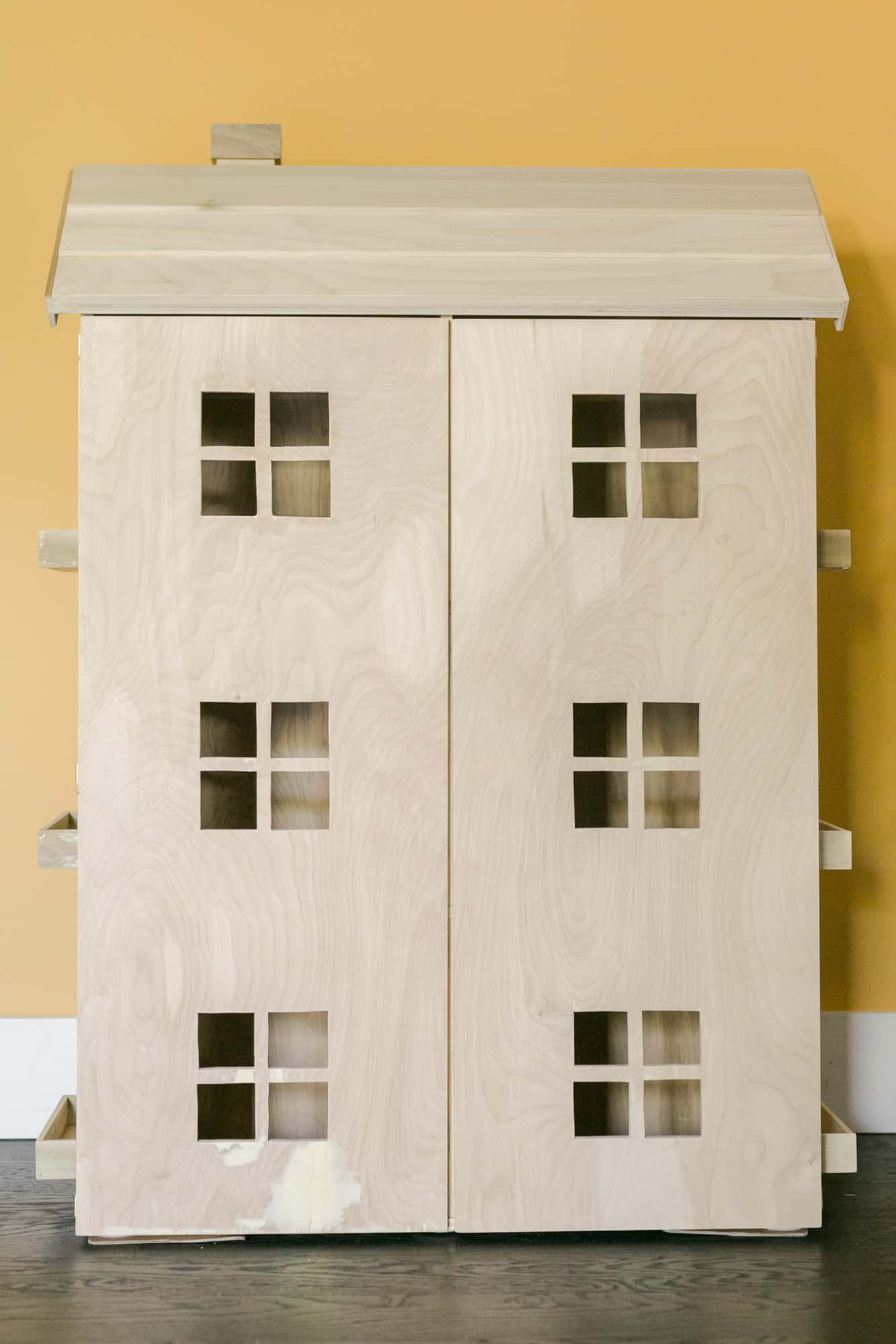An unpainted wooden dollhouse.