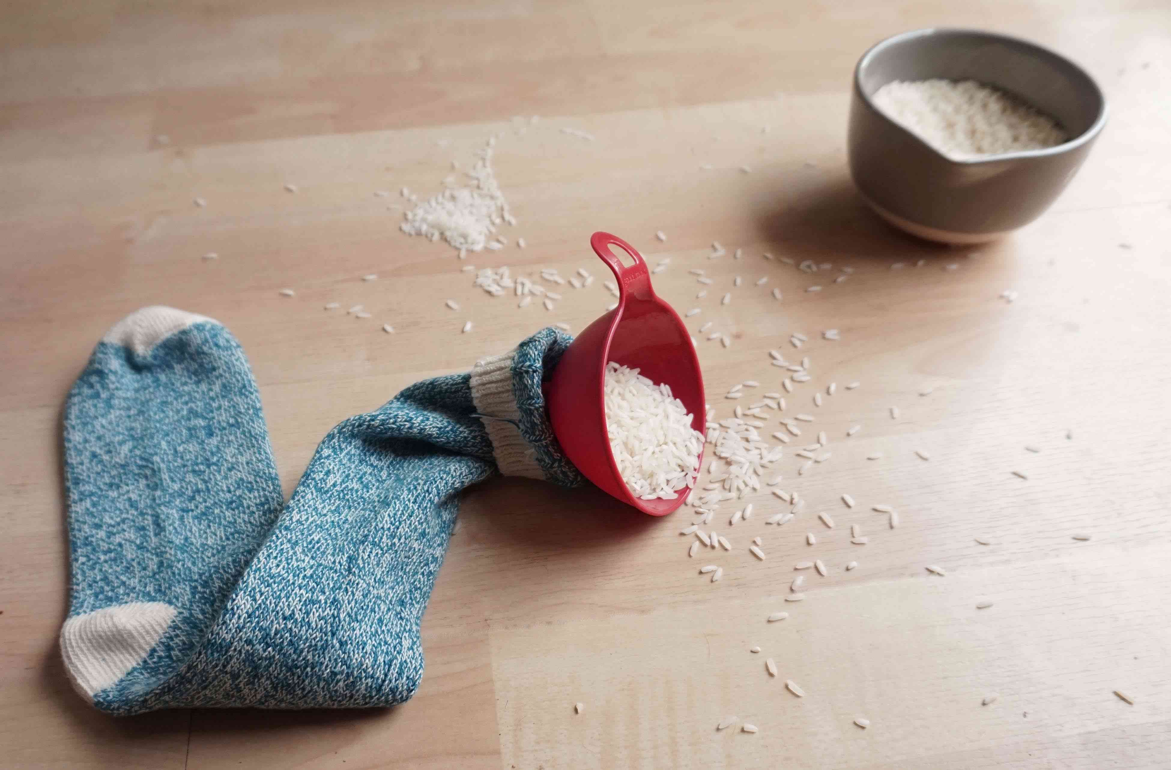 A funnel willed with rice grains inside a blue sock.