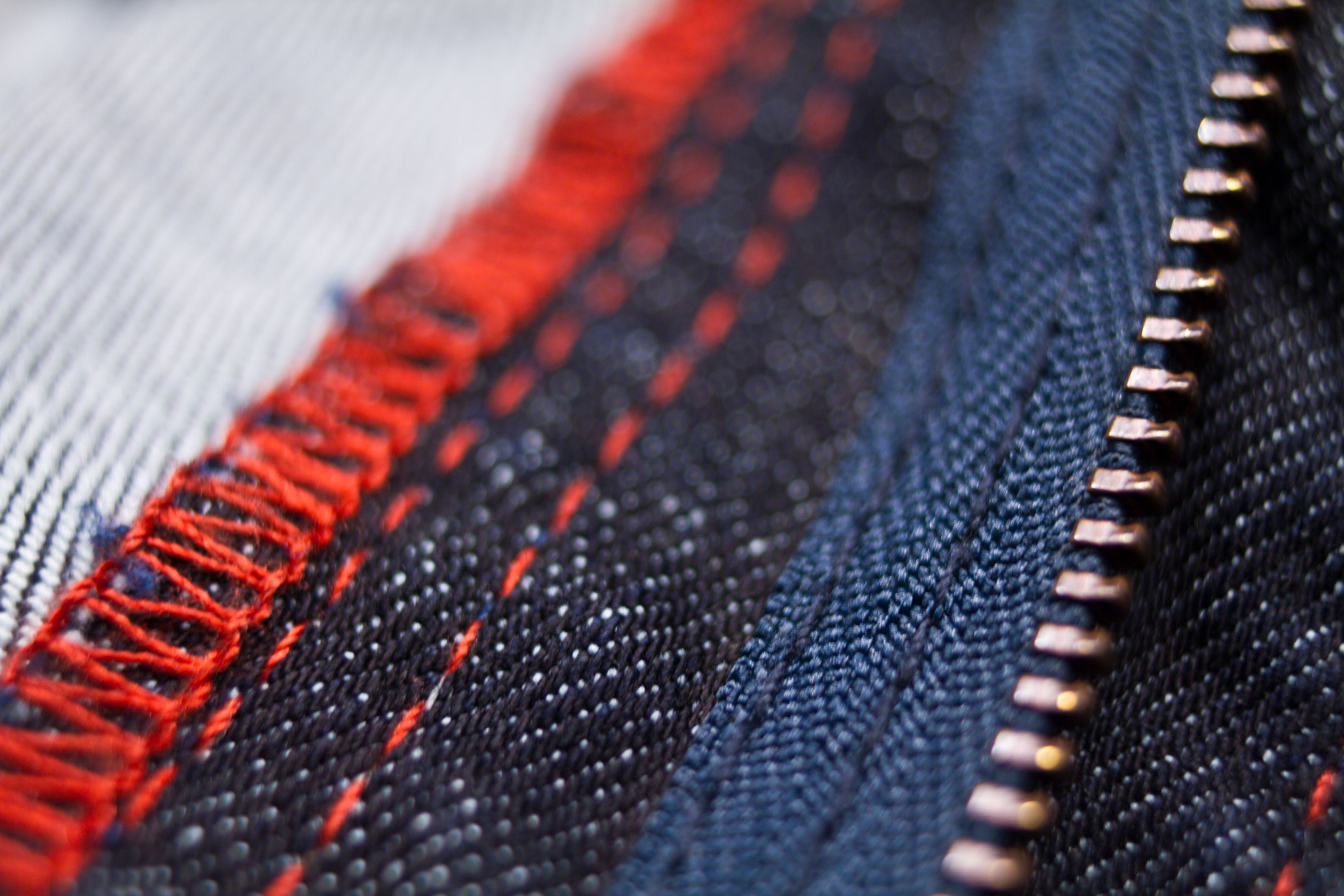 Red and blue jeans close up of zipper and stitching