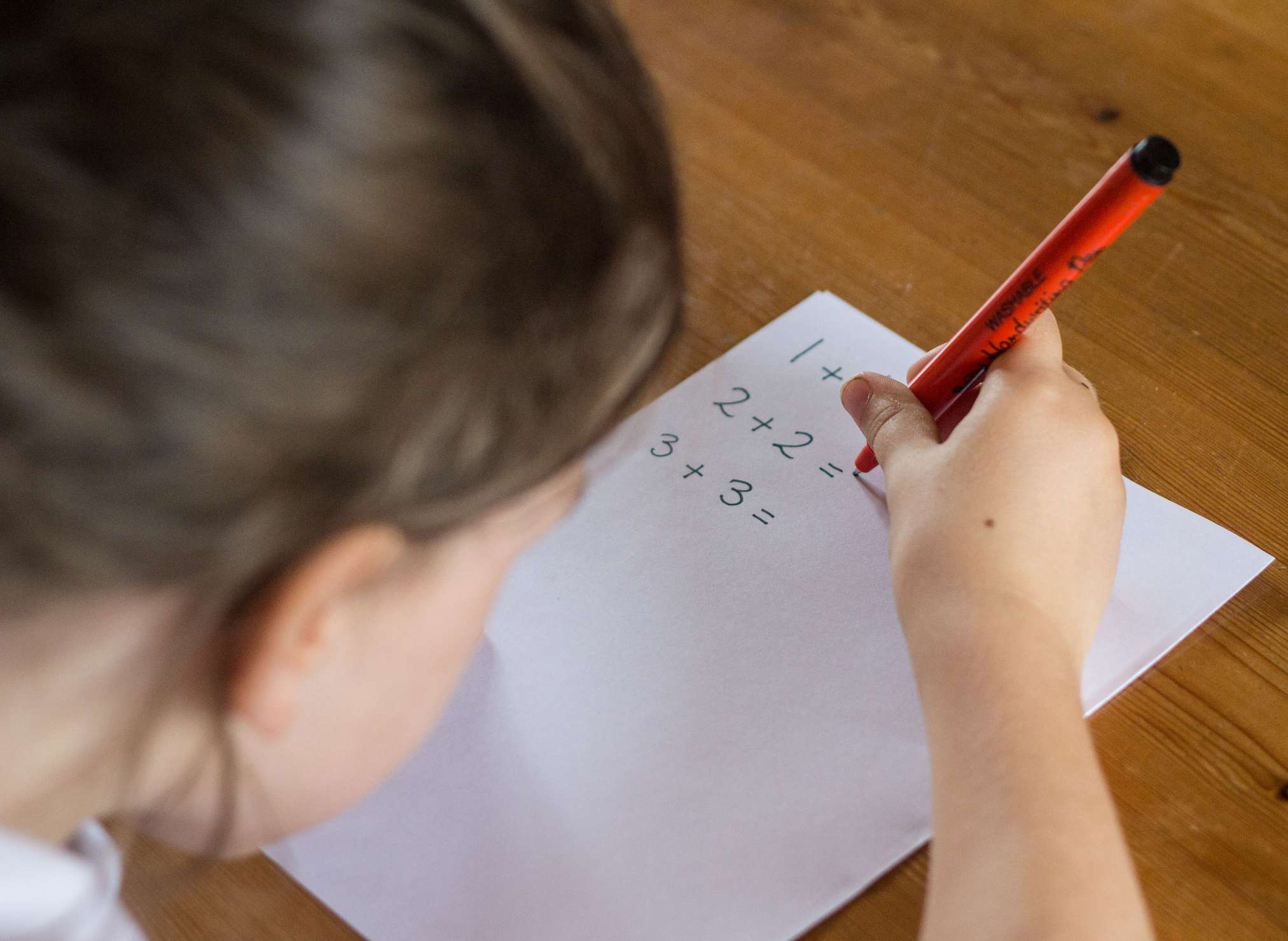 Young girl working out simple maths problems.