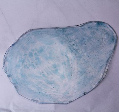 A piece of textured styrene colored to resemble a water surface for a dollhouse koi pond.