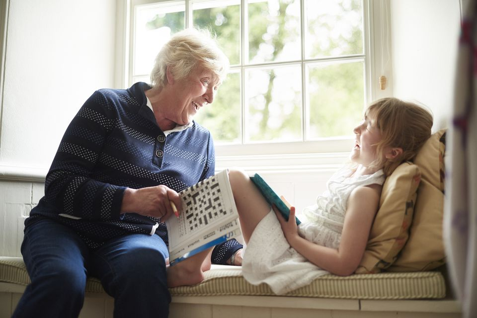Grandmother and granddaughter with crossword puzzle
