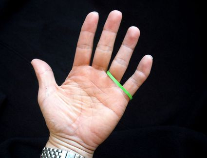colorful rubber band wrapped around ring and pinky fingers