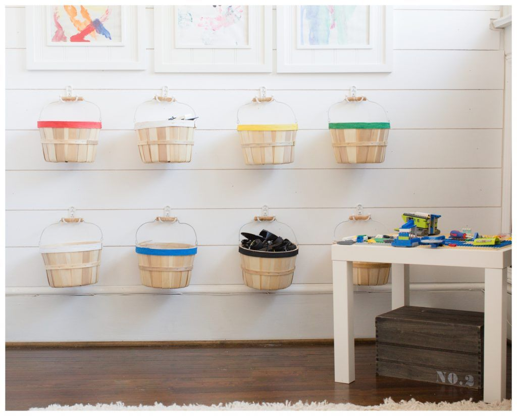 Baskets hanging on a wall to store legos