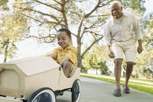 Grandfather pushing grandson in soapbox car