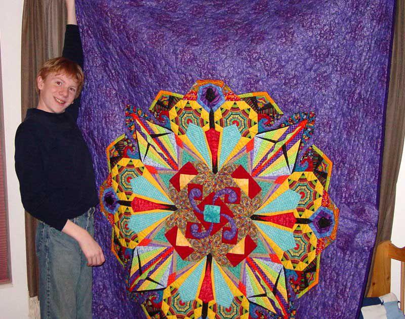 Boy next to a purple kaleidoscope quilt.