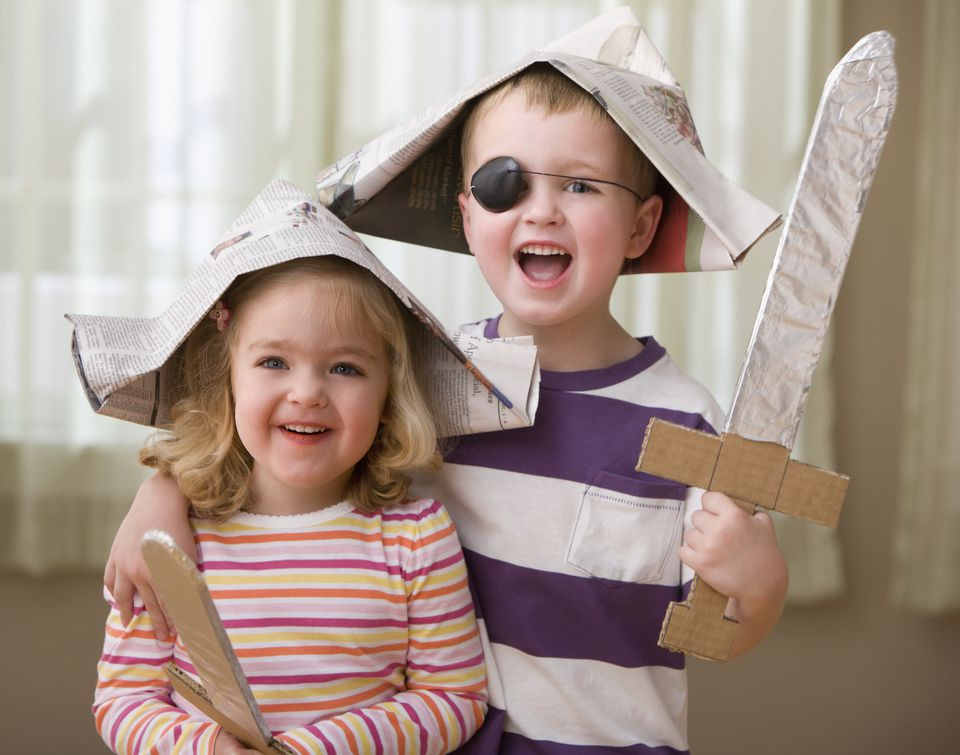 A young brother and sister wearing paper pirate hats and holding cardboard swords.