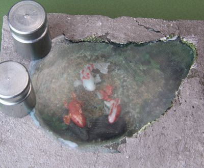 Textured styrene sheet is glued above a dolls house scale koi pool to finish off the water surface.