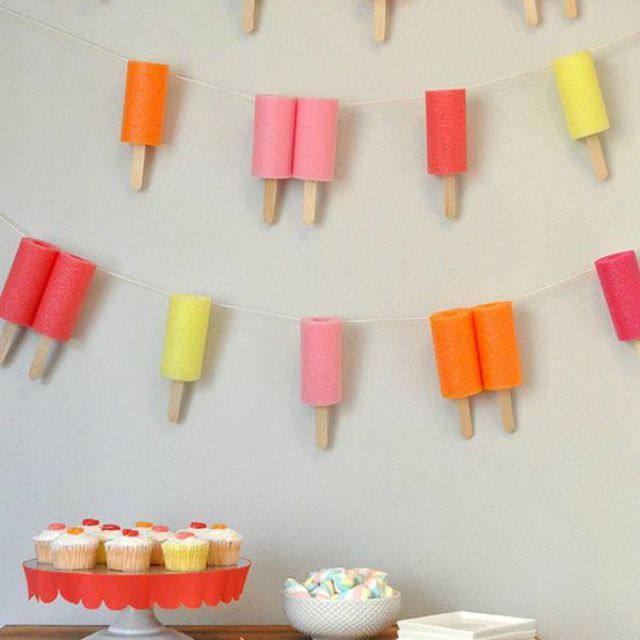 Pool noodle Popsicles hanging from the wall with tray of cupcakes sitting on a wooden table.