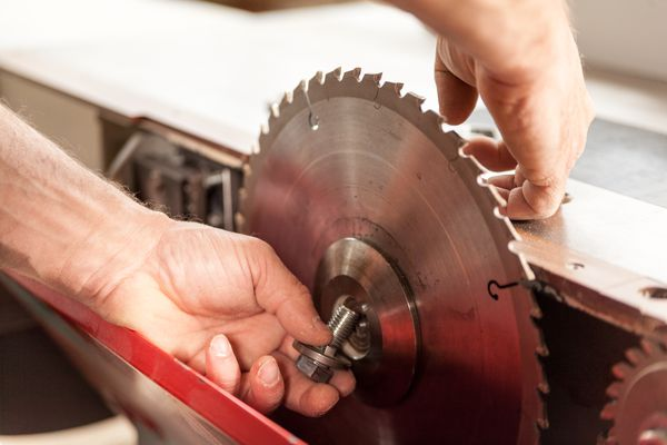woodworker changing a sawblade on his miter saw