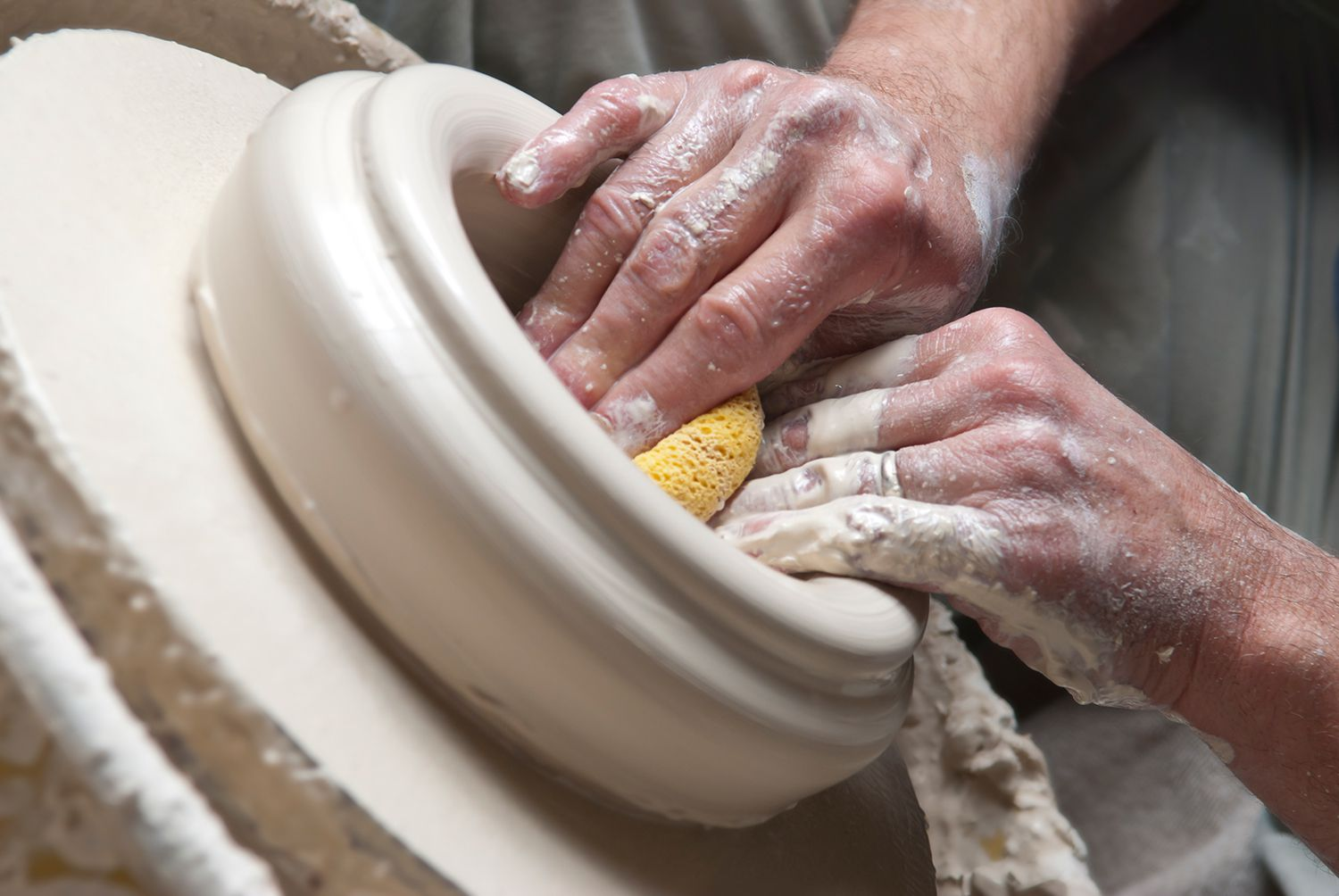 Potter uses sponge to shape bowl on pottery wheel.