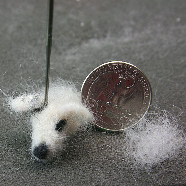 Felted ears and markings attached to a dollhouse miniature felted dog's head.