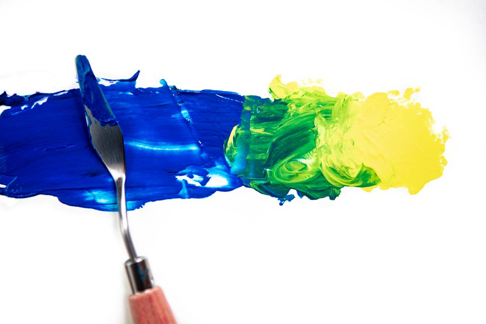 Paint being blended with palette knife, Yellow and Blue makes Green